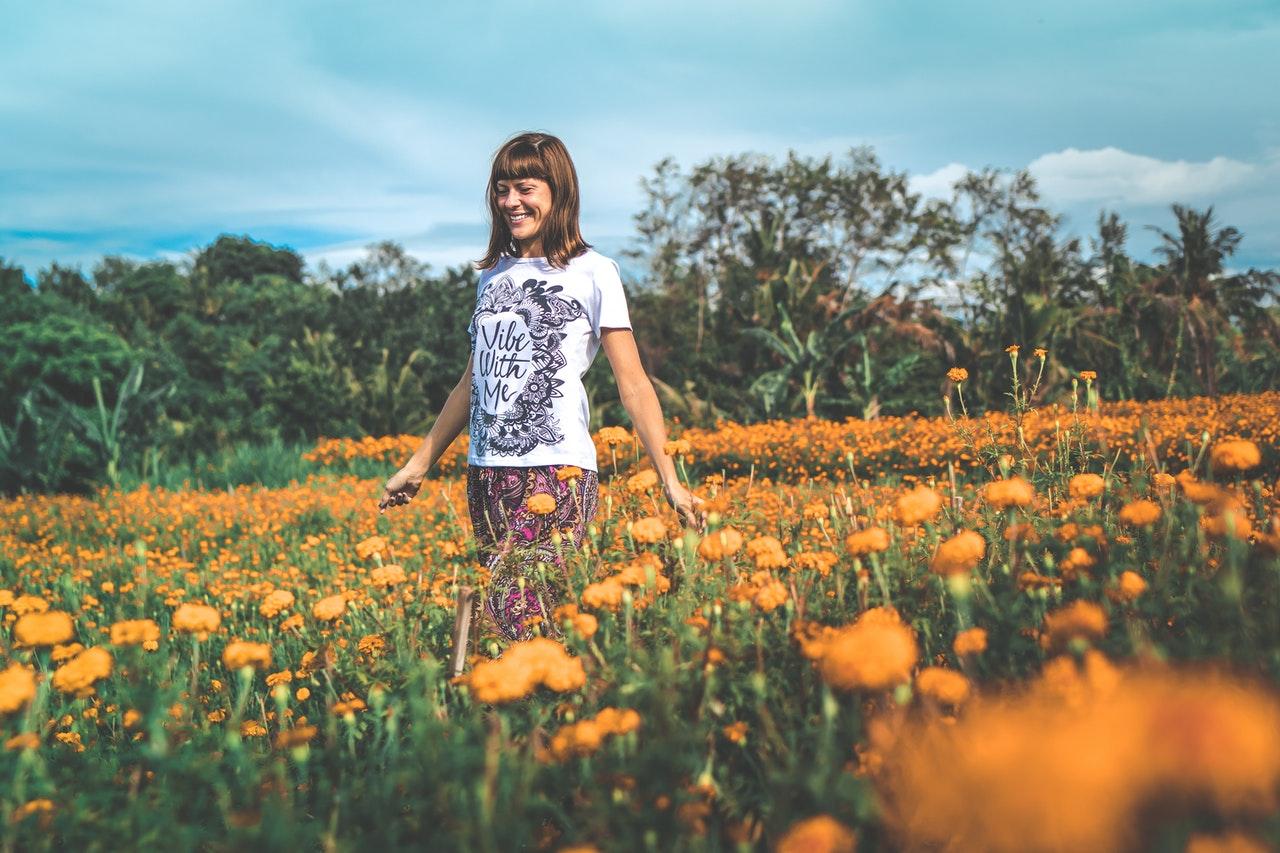 Dame går igennem mark med blomster