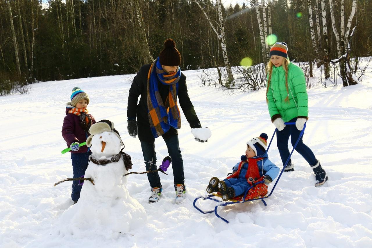 Familie leger i sne med vintertøj