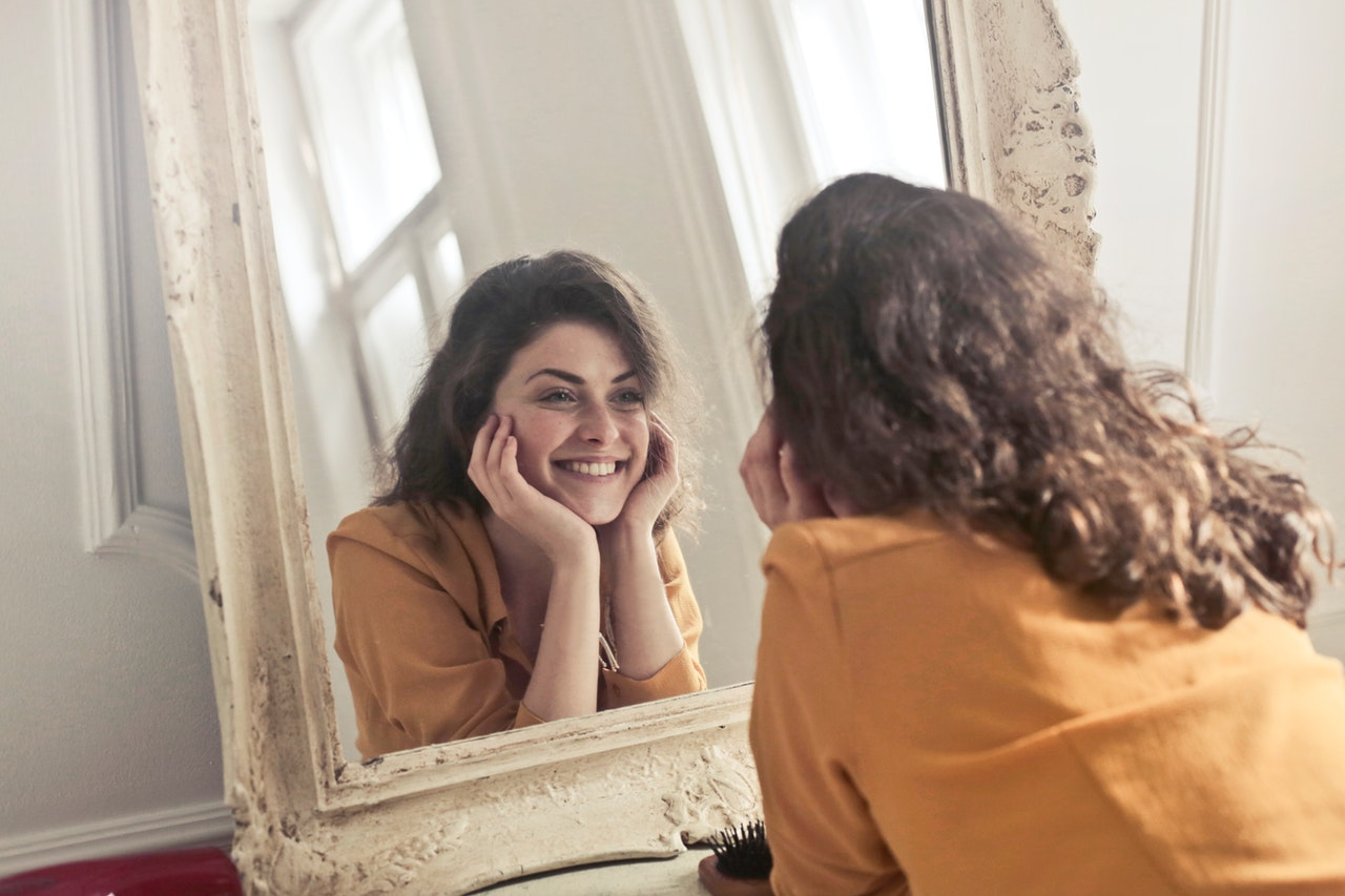 Kvinde kigger sig i spejlet og er glad