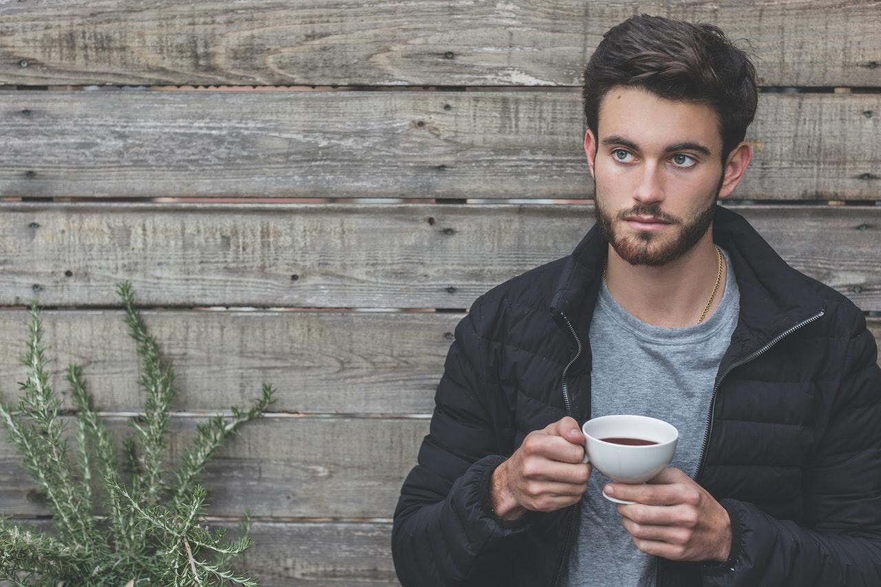 Mand drikker kaffe udenfor og flot hår