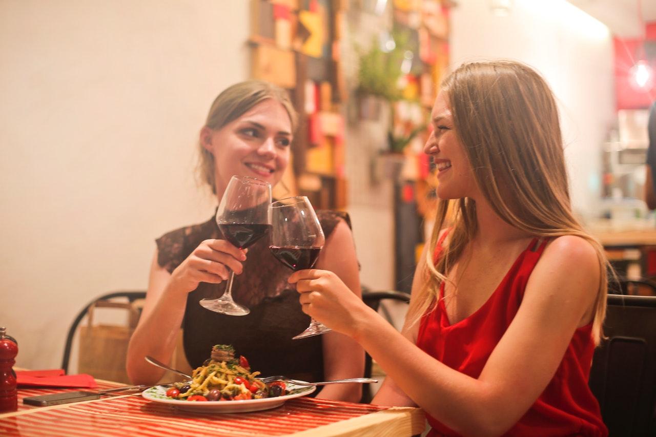 To kvinder drikker vin sammen og spiser